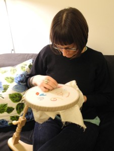 Hannah embroidering - trying to finish my sampler,  this embroidery hoop stand is amazing - it leaves you with both hands free to sew!